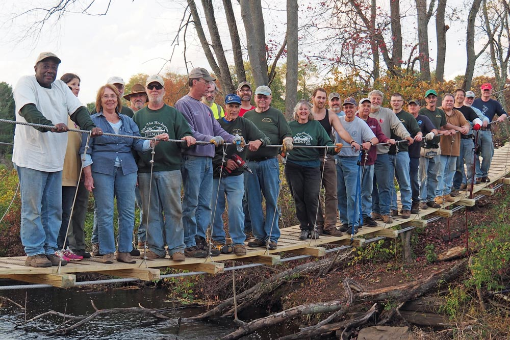 volunteers all standing on newly installed bridge