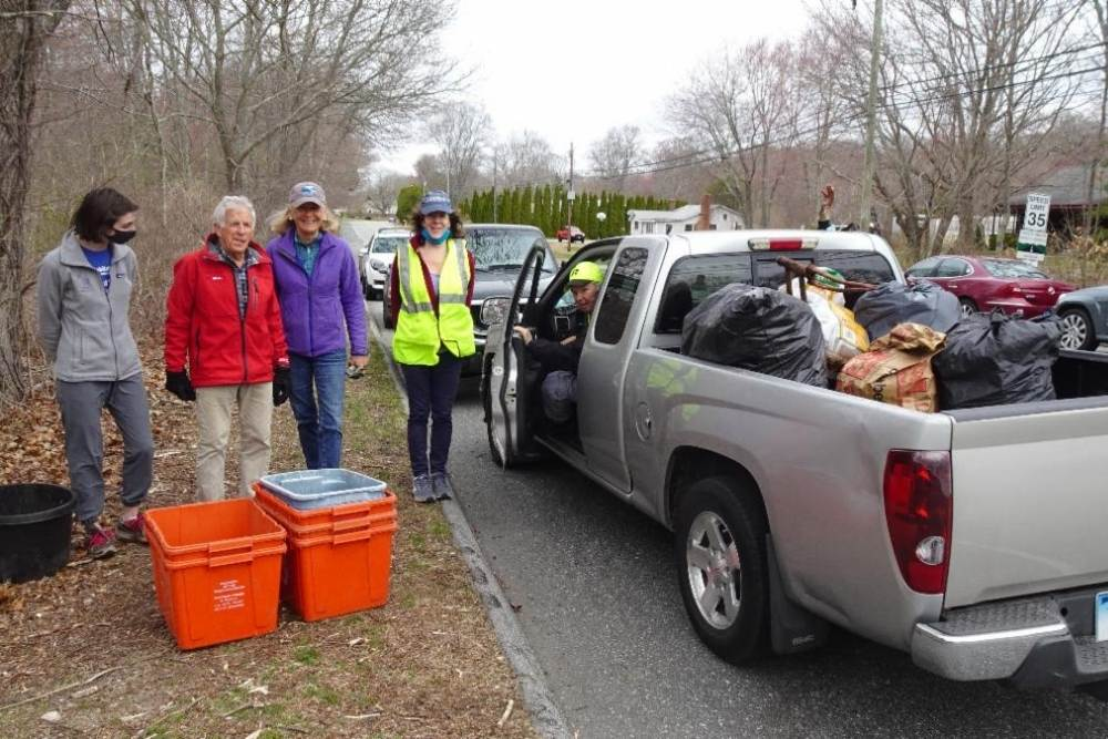 Four adults standing on the side of the road with orange buckets in front of them, and one adult sitting in a tan truck