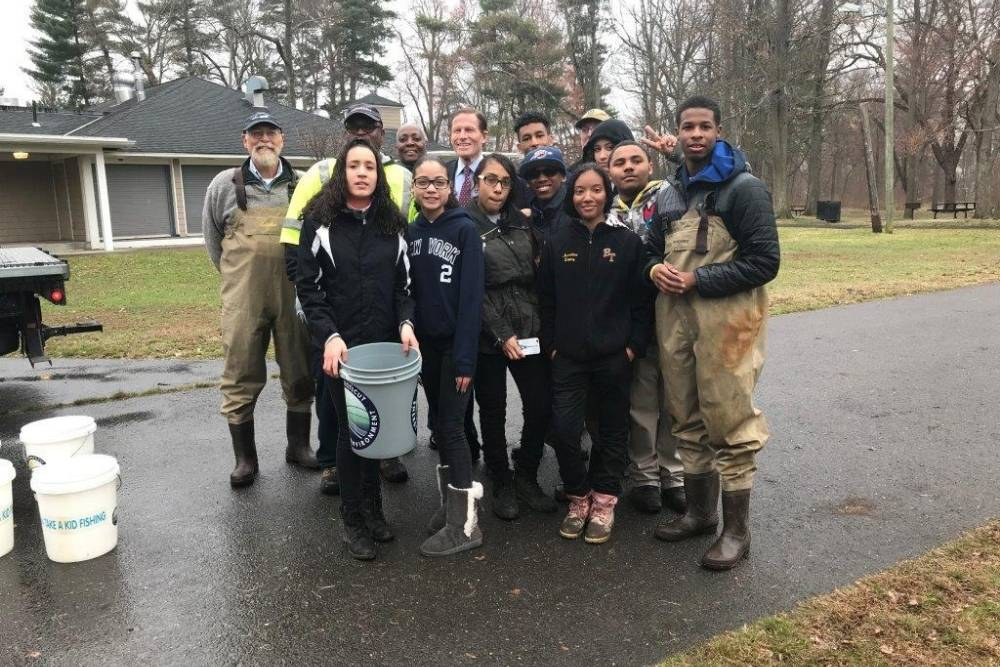 Diverse group of adults and students posing on a driveway with buckets from CT DEEP